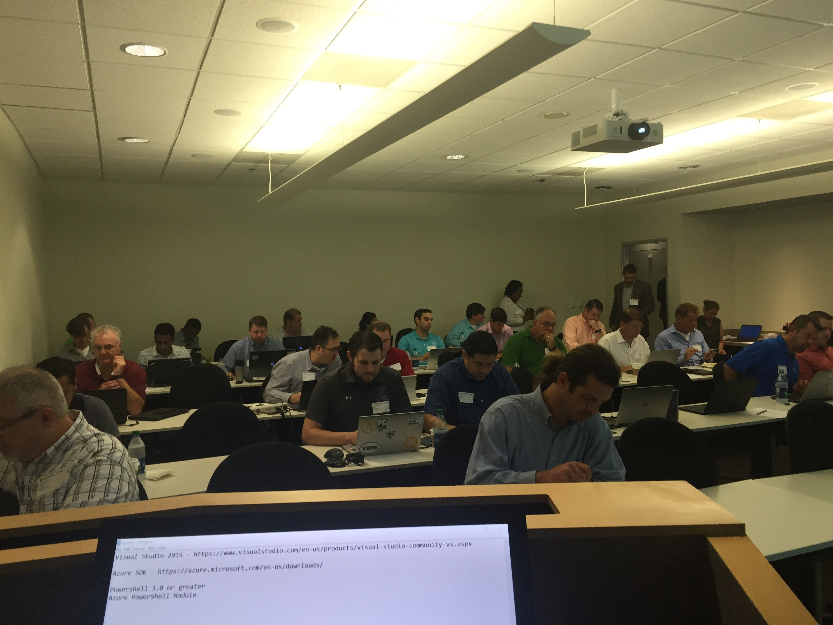 A classroom-style room full of men working on laptops